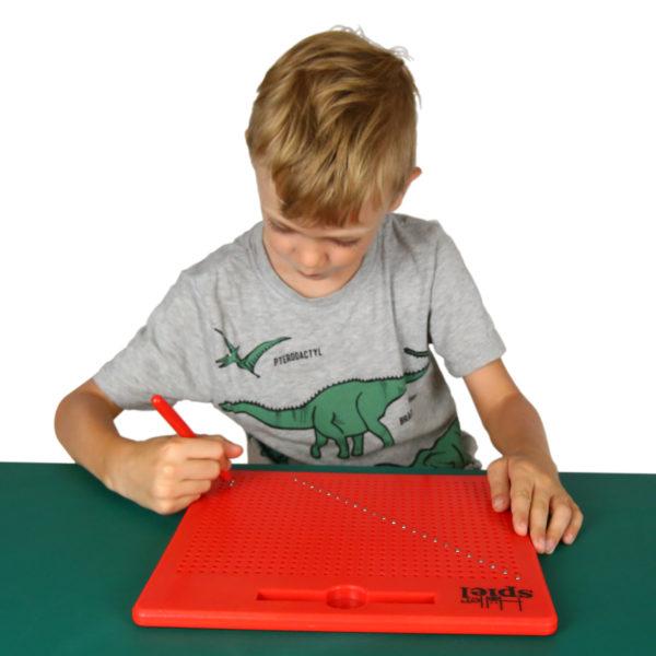 Kind malt mit Magnetstift auf der Magnetzeichentafel
