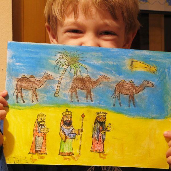 Ein Kind hält ein gestempeltes und ausgemaltes Bild der heiligen drei Könige mit drei Kamelen im Hintergrund.