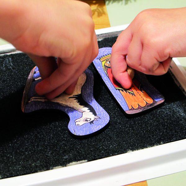Zwei Kinderhände drücken Stempel in ein großes Stempelkissen.