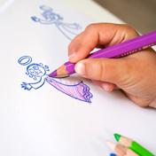 Foto: Kinderhand malt mit violettem Buntstift gestempelten Engel aus