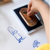 Foto: Kinderhand drückt Stempel in Stempelkissen