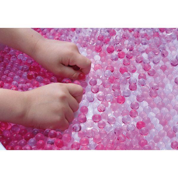Foto: Kinderhände spielen mit rosa gefärbten Wunderperlen