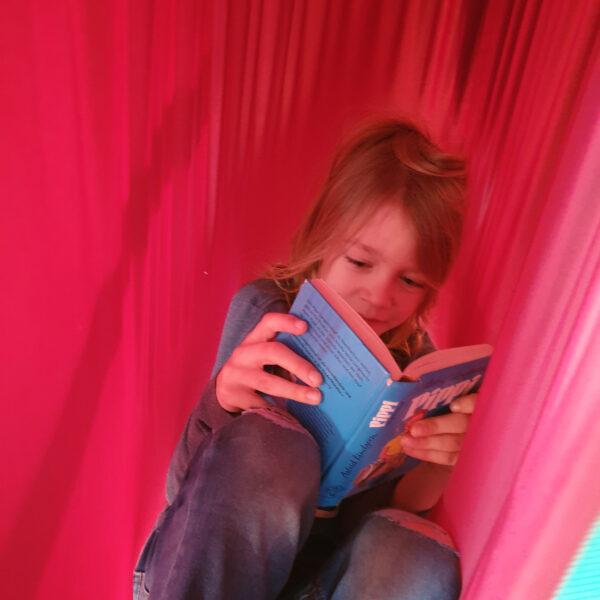 Kind liest in Erlebnistuch als Hängehöhle
