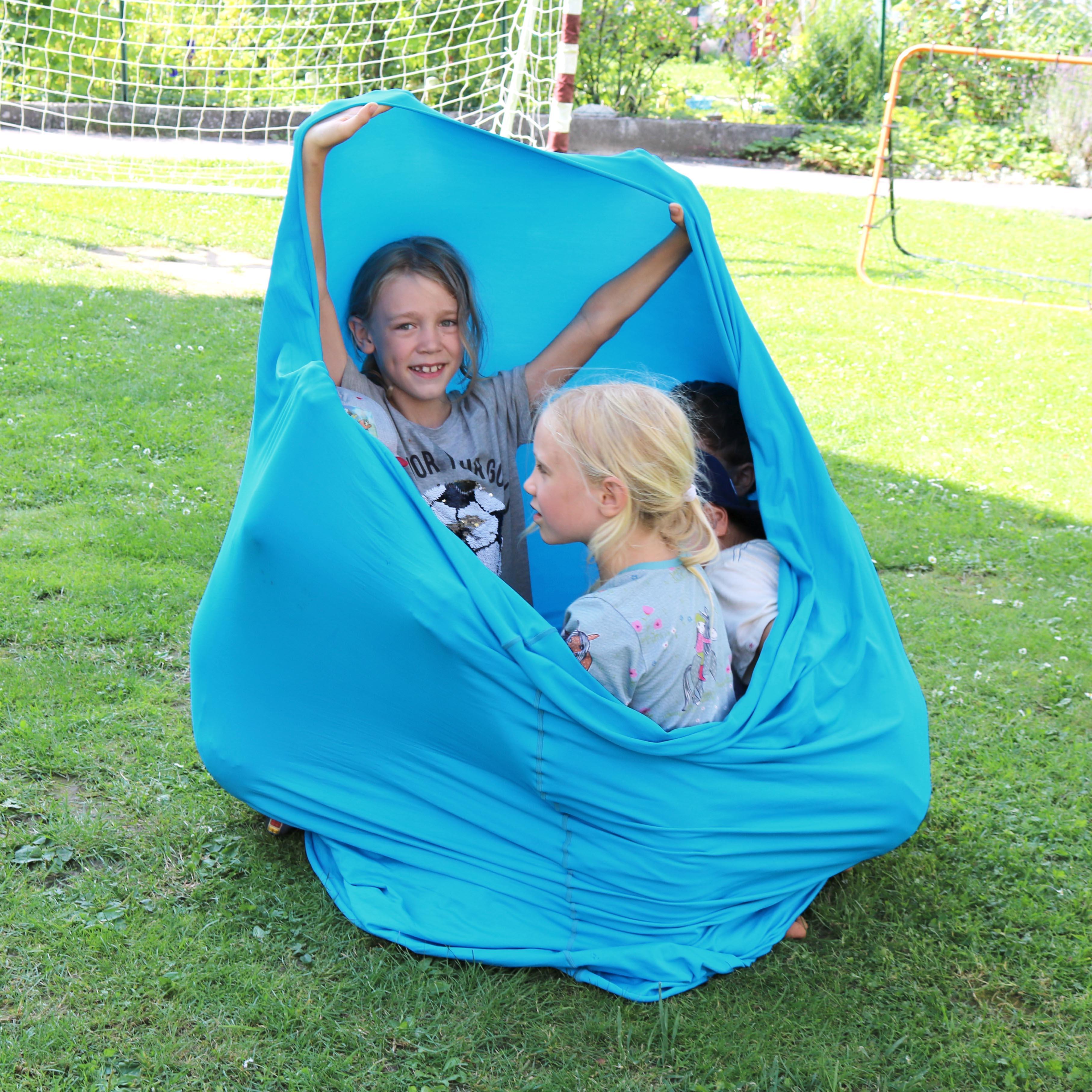 Kinder machen sich eine Höhle aus einem Erlebnistuch