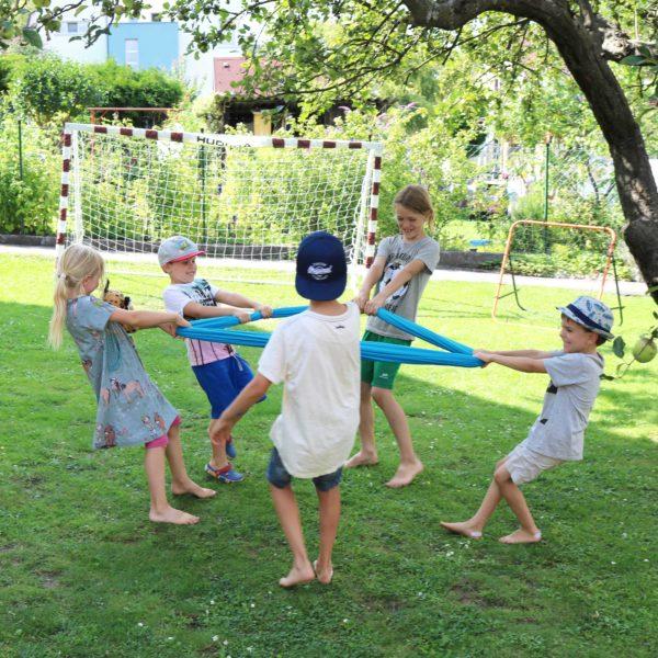 Kinder spielen ein Kreisspiel mit dem Erlebnistuch