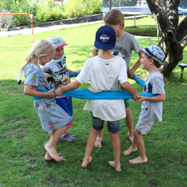 Kinder tanzen in einem Kreis im Erlebnistuch