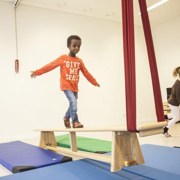 Foto: Kind im Turnsaal macht Übung mit Erlebnistuch von Le Bonbond