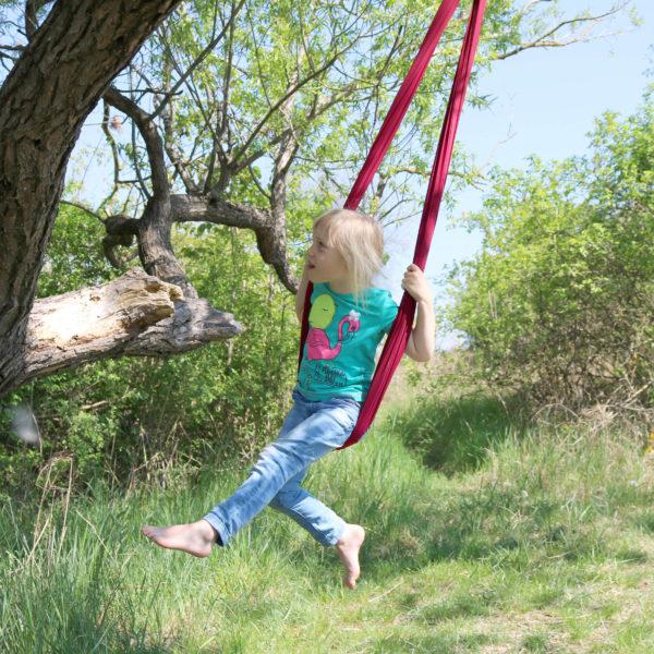 Foto: Kind schaukelt mit hängendem Erlebnistuch in der Natur