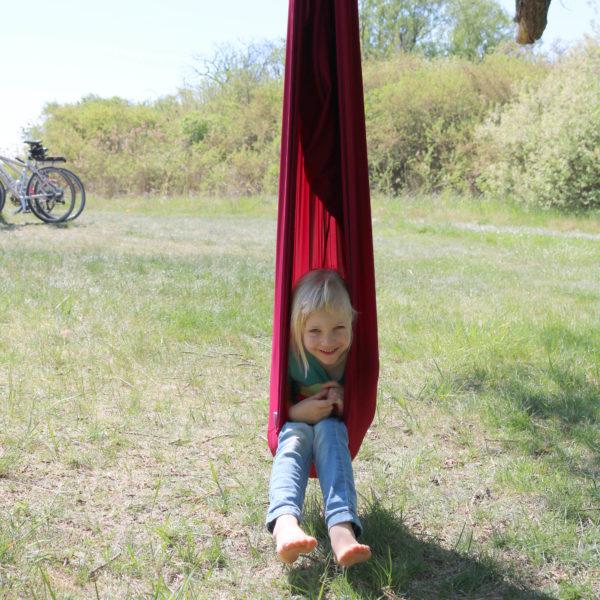 Foto: Kind sitzt in hängendem Erlebnistuch wie in einem Hängesessel