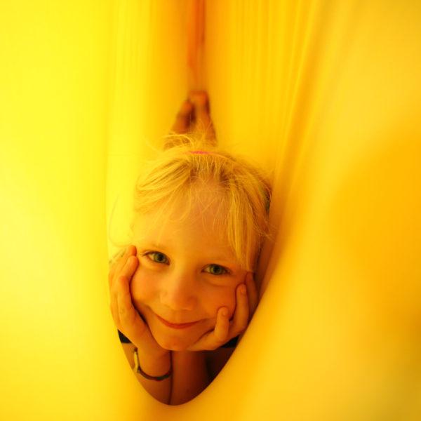 Foto: Kind liegt in gelbem Erlebnistuch, durch den Stoff strahlt das Licht