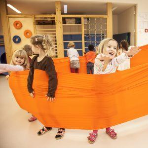 Foto: Kinder im Turnsaal machen Übung mit Erlebnistuch von Le Bonbond