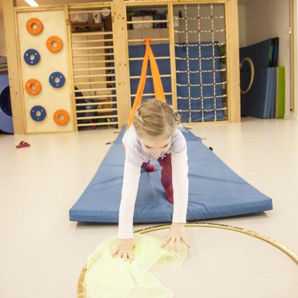 Foto: Kind im Turnsaal macht Übung mit Erlebnistuch