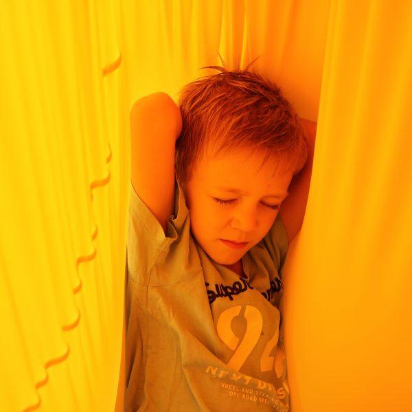 Foto: Kind entspannt in gelbem Erlebnistuch von Le Bonbond