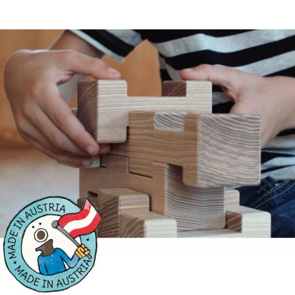 Kinderhände bauen einen Turm aus 4/4 Holzbausteinen. Daneben eine Grafik mit dem Text: Made in Austria.