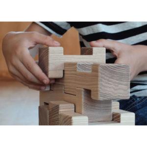 Kinderhände bauen einen Turm aus 4/4 Holzbausteinen
