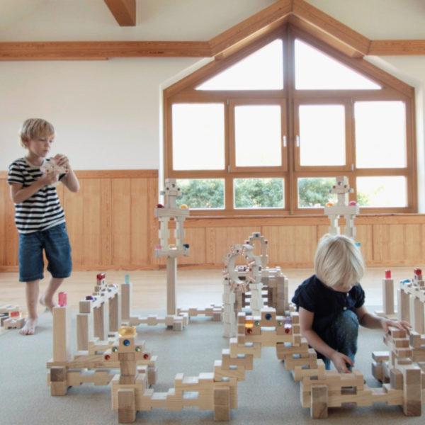 Kinder bauen große Burg aus 4/4 Holzbausteinen hergestellt in Österreich