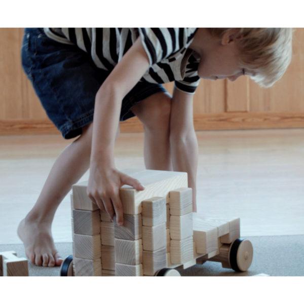 Kind spielt mit großem Fahrzeug aus 4/4 Holzbausteinen hergestellt in Österreich