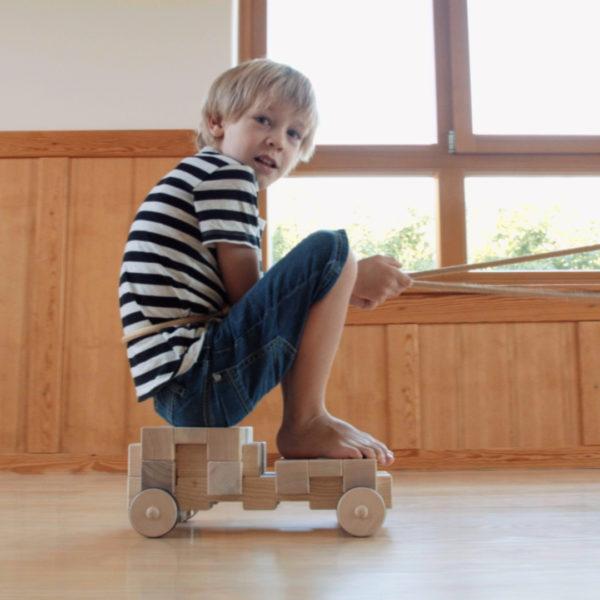 Kind fährt auf großem Fahrzeug aus 4/4 Holzbausteinen hergestellt in Österreich