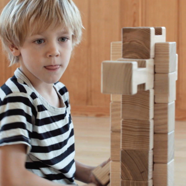 Kind baut hohen Turm aus 4/4 Holzbausteinen hergestellt in Österreich