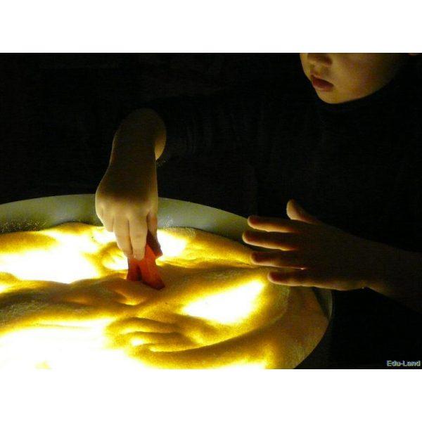 Foto: Kind spielt mit Gries auf gelb beleuchteter Leuchttonne
