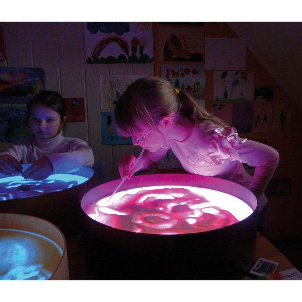 Foto: Kinder spielen mit Gries auf beleuchteten Leuchttonnen