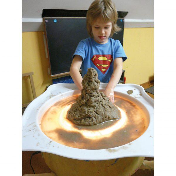 Foto: Kind matscht mit Sand und Wasser im Wannenaufsatz auf einer beleuchteten Leuchttonne