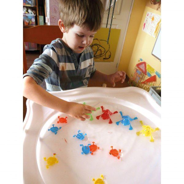 Foto: Kind spielt mit Wasser und Plastikfröschen im Wannenaufsatz