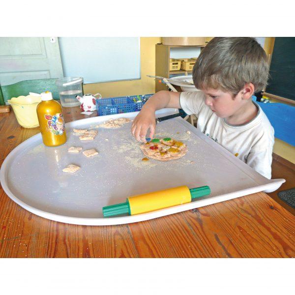 Foto: Kind spielt mit Knete auf Tischaufsatz