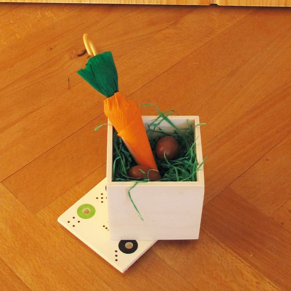 Ab in die Box Spiel aus Holz offen mit Ostergras und Süßigkeiten gefüllt