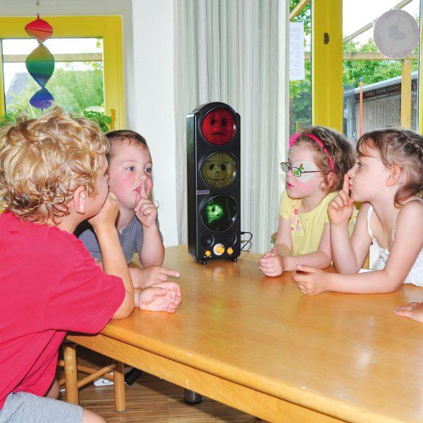 Kinder sitzen rund um Lärmampel und zeigen durch den Zeigefinger vor dem Mund, dass man leise sein soll.