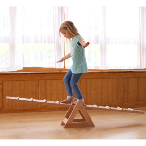 Kindergartenkind balanciert über Laufwippe