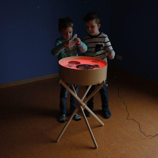 Foto: 2 Kinder legen Bilder auf die Leuchttonne