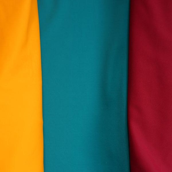 Die drei Farben der Erlebnistücher: gelb, petrol und brombeer