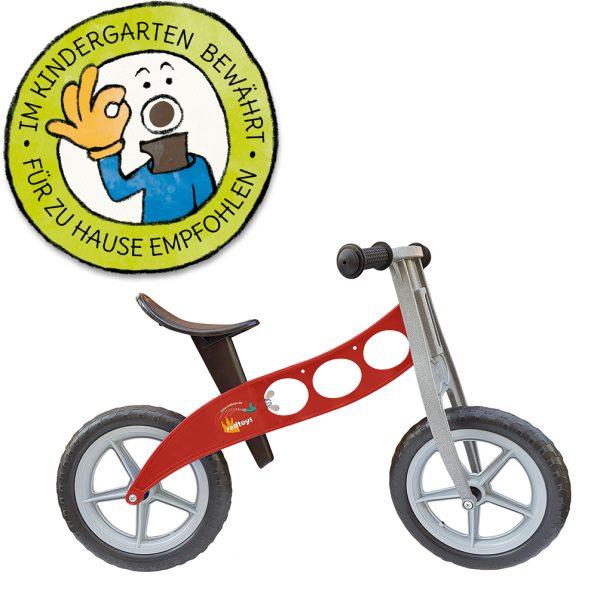 """Foto: rotes Kinder-Laufrad """"Feuerwehr"""" neben Grafik """"Im Kindergarten bewährt - für zu Hause empfohlen"""""""