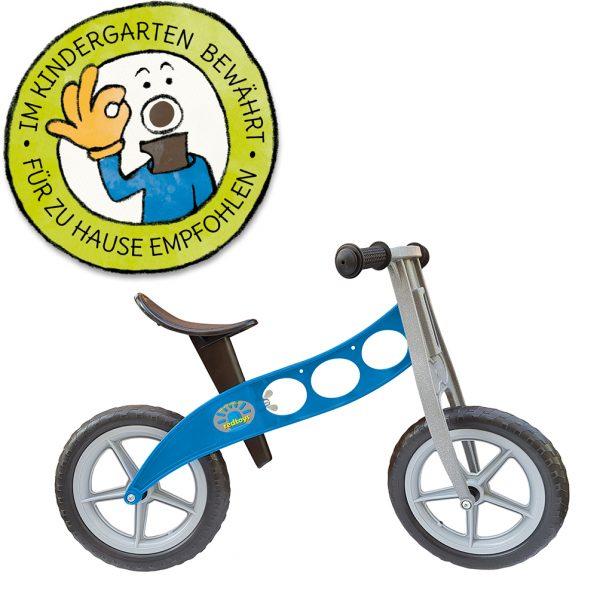 """Foto: blaues Kinder-Laufrad """"Polizei"""" neben Grafik """"Im Kindergarten bewährt - für zu Hause empfohlen"""""""