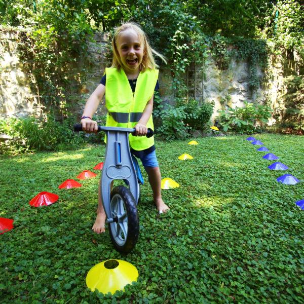 Kind trägt eine Warnweste und fährt mit dem Laufrad einen Parcours zwischem Markierungskegeln