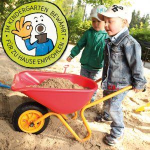 Foto: Kinder spielen in der Sandkiste mit der Kinder-Schubkarre