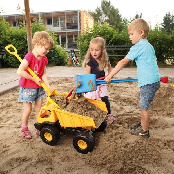 Foto: Kinder beladen Riesen Kipplaster mit Sand in der Sandkiste