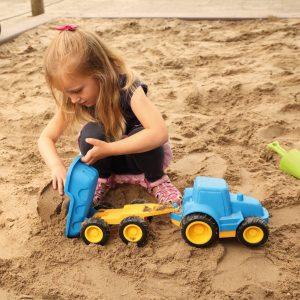 Foto: Kind spielt mit Traktor mit Anhänger in der Sandkiste