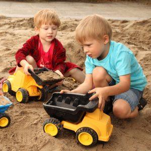 Foto: Kinder spielen mit großem Kipplaster in Sandkiste