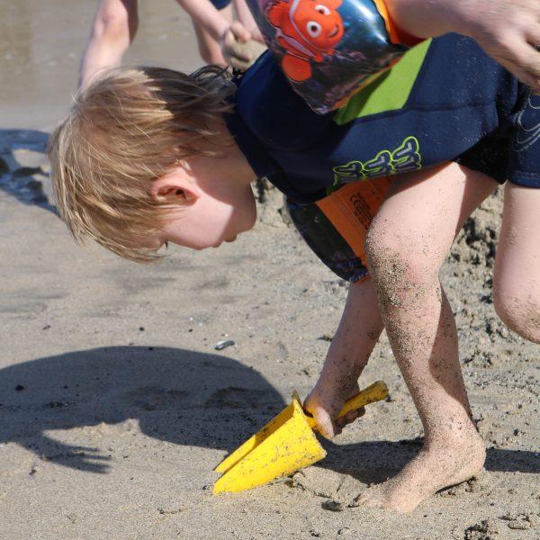 Foto: Kind gräbt mit gelber Sandschaufel im Sand