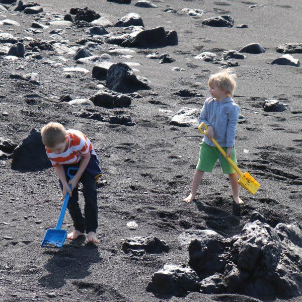 Foto: Kinder spielen mit großen Kinderschaufeln im Sand
