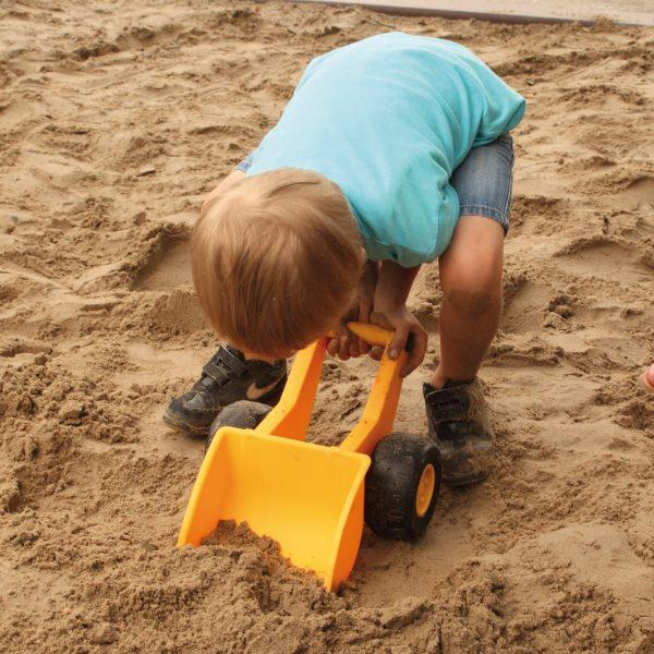 Foto: Kind schaufelt Sand mit dem Handbagger