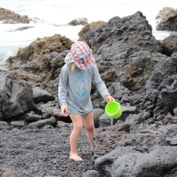 Foto: Kind gießt Wasser aus dem Mini-Sandkübel