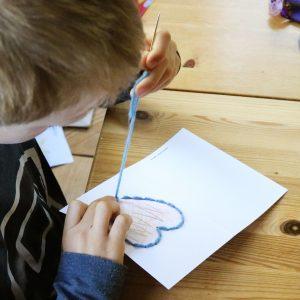 Foto: Kind näht mit Wolle das Herz auf einer Grußkarte nach