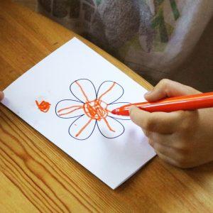 Foto: Kinderhand bemalt eine Grußkarte mit Blume