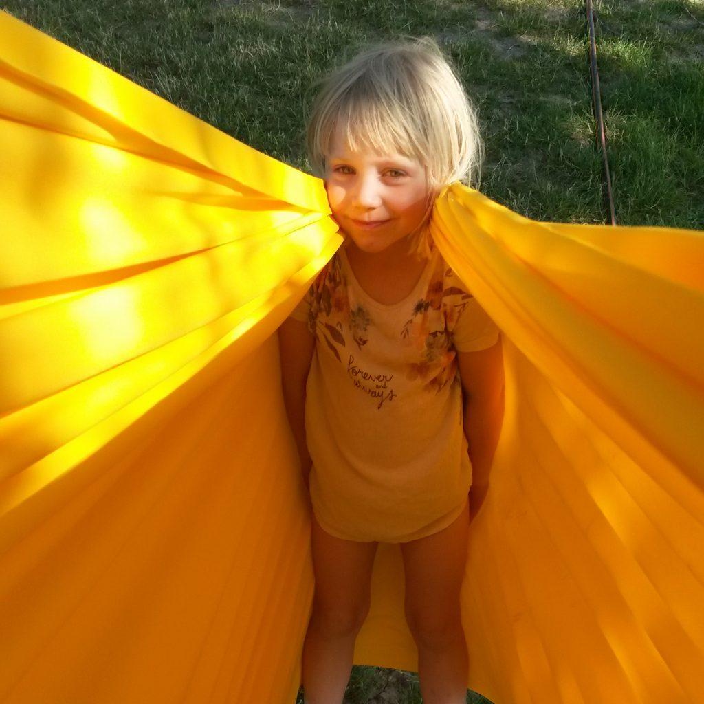 Foto: Kind lehnt sich in gelbes Erlebnistuch