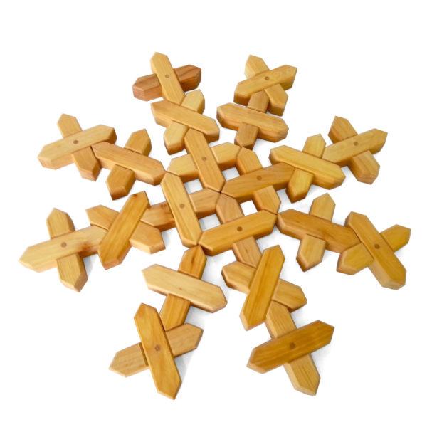 Schneeflocke gelegt aus X-förmigen Holzbausteinen