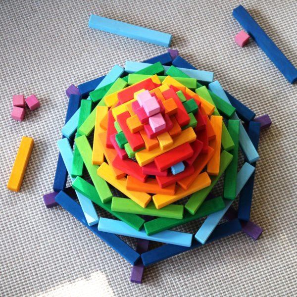 Ein Turm in Regenbogenfarben aus den Holzbausteinen der Bautreppe von Bauspiel