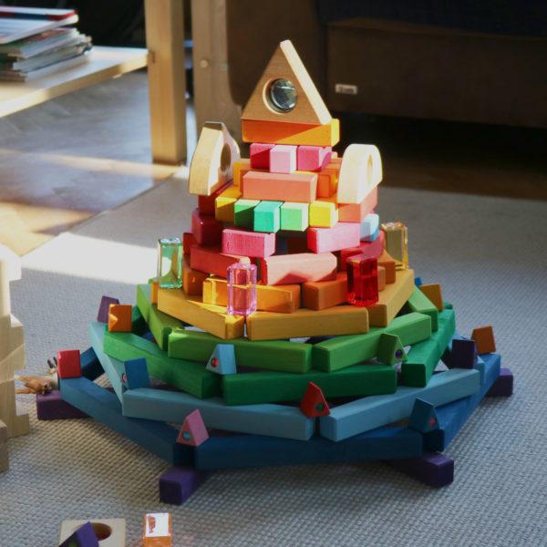 Ein Turm in Regenbogenfarben aus den Holzbausteinen der Bautreppe und anderen Bausteinen.